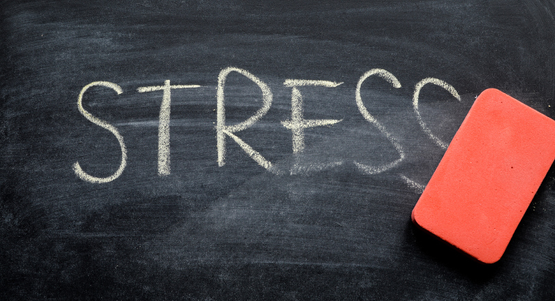 An eraser rubs out the word stress on a blackboard