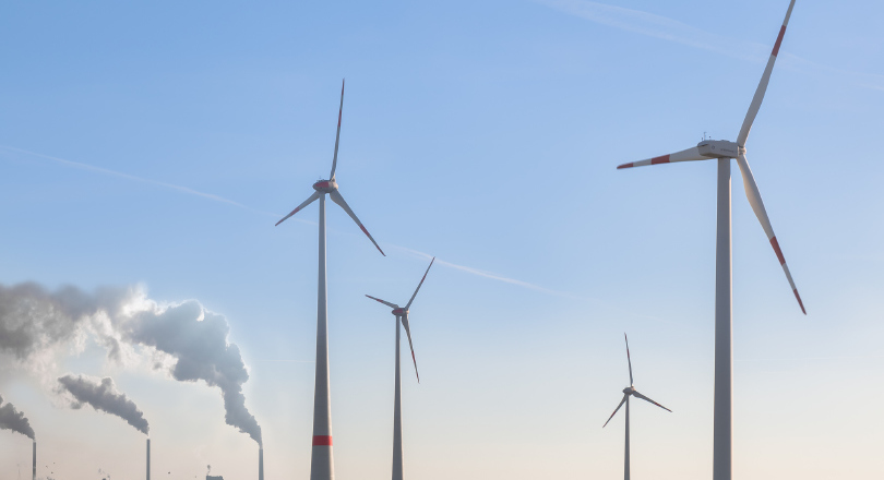 Wind turbines in front of coal plant