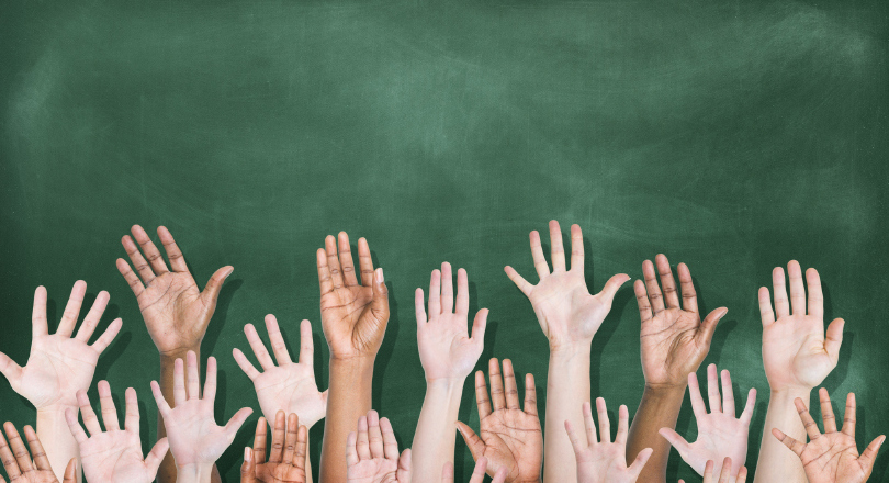 raised hands in front of blackboard